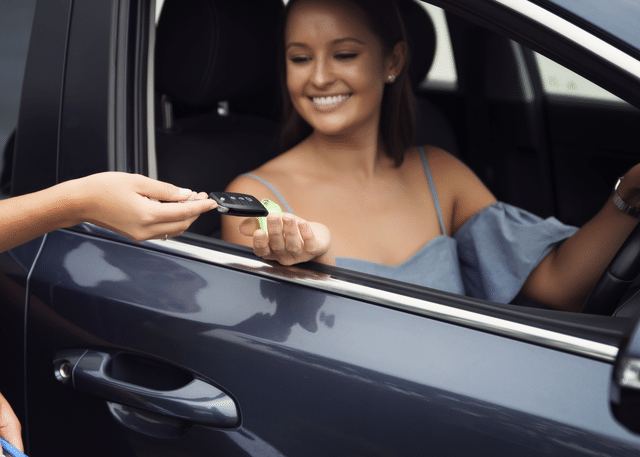 smiling woman in car receiving car keys