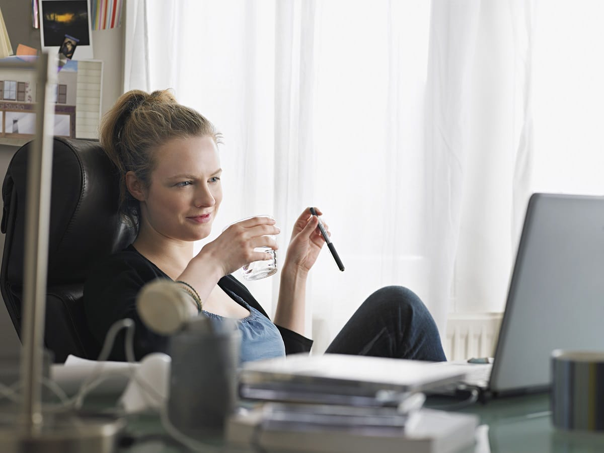 lady sitting on her desk holding a pen and glass of water looking at her laptop