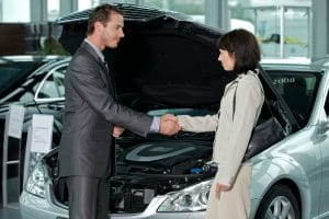 man and woman shaking hands in front of car