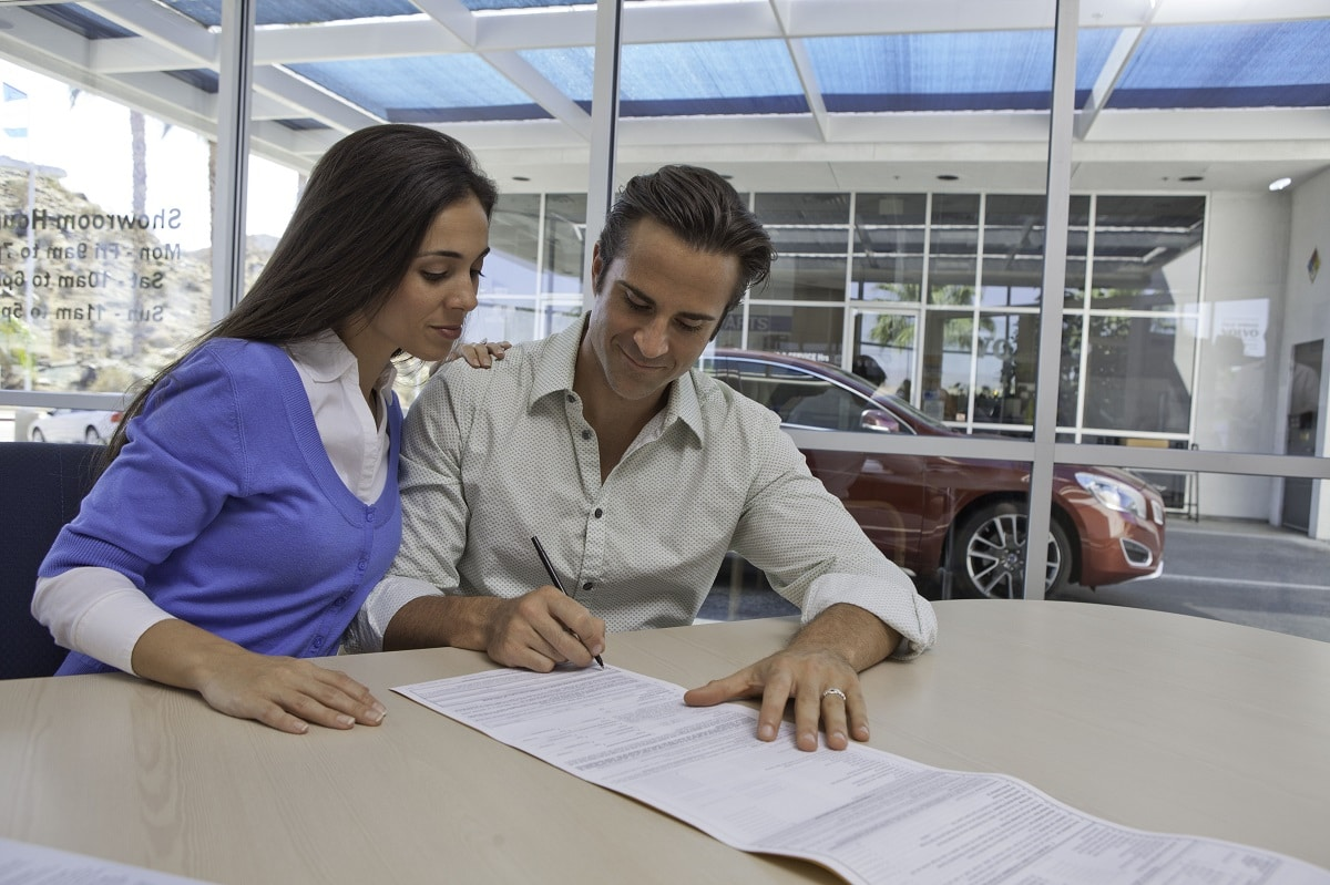 couple signing for a car